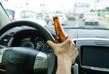 Person driving with a beer in hand